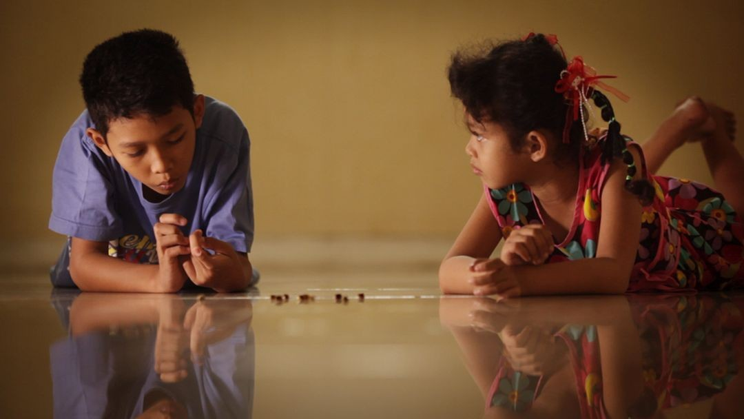 Adi's children play with jumping beans in Drafthouse Films' and Participant Media's The Look of Silence. Courtesy of Drafthouse Films and Participant Media.